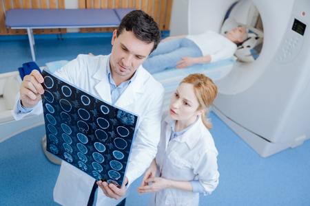 Médico profesional serio mirando los escáneres cerebrales CT Foto de archivo