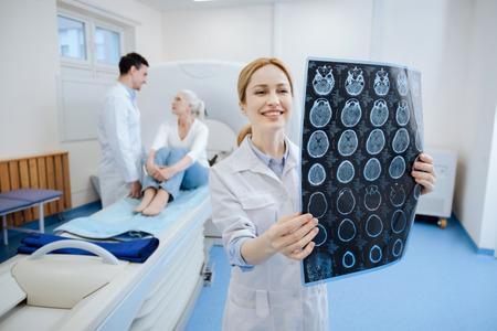脳の問題を見ていない幸せなうれしそうな医者 写真素材