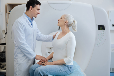 Handsome joyful doctor telling his patient a diagnosis Stock Photo