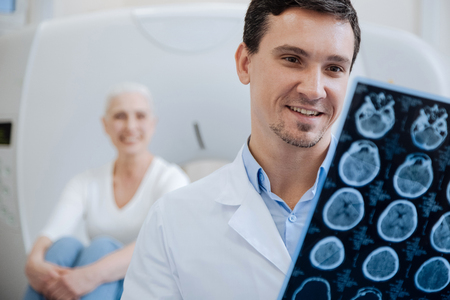 CT 스캔 결과를 보유한 행복한 긍정적 인 의사 스톡 콘텐츠