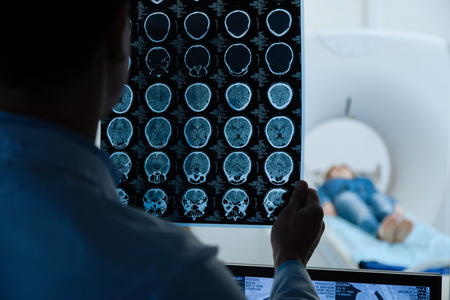 MRI scan images being examined by a doctor