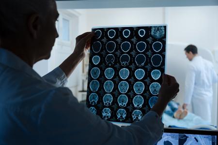 Oncologista inteligente experiente, olhando para os resultados do exame de ressonância magnética
