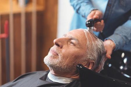 Aged man enjoying wellness procedures in the barbershop