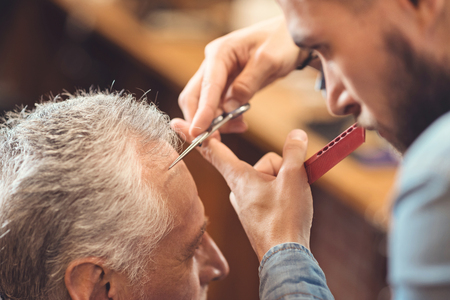 Masterful barber making hairdo of the retired client in barbershop