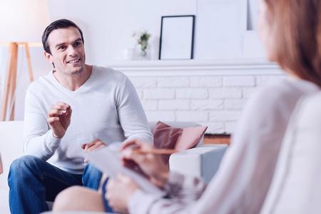 Joyful handsome man talking with psychologist