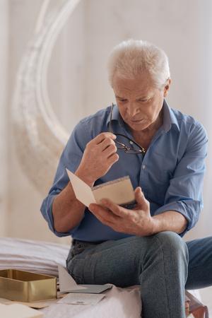 gerontology: Unhappy gloomy man holding an old postcard Stock Photo