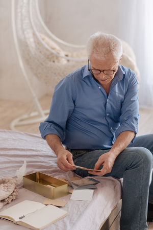 gerontology: Pleasant senior man turning over old letters