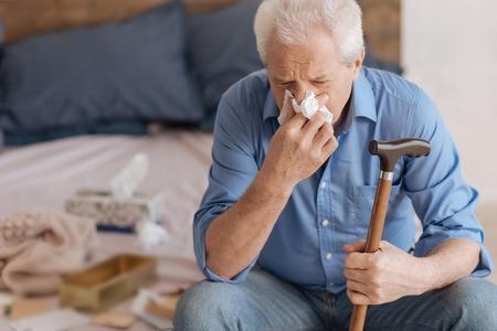 gerontology: Unhappy senior man using a paper tissue Stock Photo