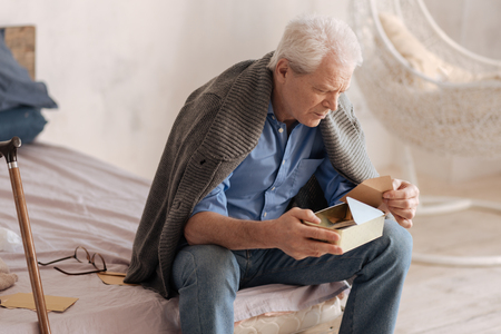 Moody senior man taking a letter out of the box Stock Photo