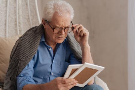 gerontology: Sad pessimistic man fixing his glasses Stock Photo
