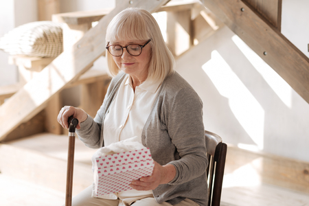 Sad elderly woman looking at the present Stock Photo