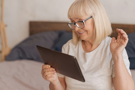 social work aged care: Cheerful positive woman looking at the tablet screen