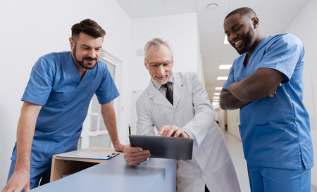 Cheerful old physician using gadget with colleagues at work