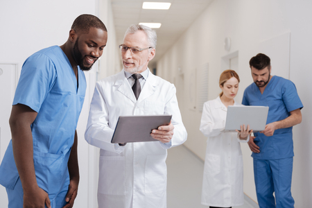 Old smiling pediatrician testing modern device at work