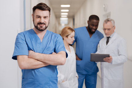 Handsome mature doctor standing in the clinic Stock Photo