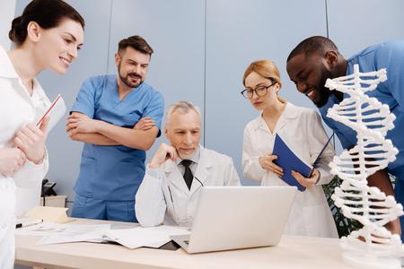 up code: Elderly doctor enjoying teaching students in medical university