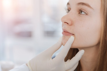 Proficient dermatologist examining patient face in the clinic Stock Photo