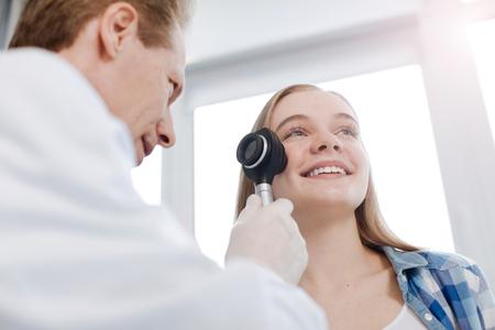 Lterer Spezialist, der die Haut des Patienten bei der Arbeit erforscht Standard-Bild - 76631494
