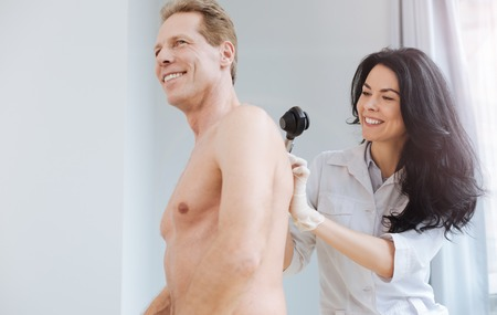 Pleasant medical specialist using dermatoscope for skin examination at work