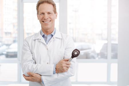 hospital patient: Delighted senior practitioner holding professional instrument at work