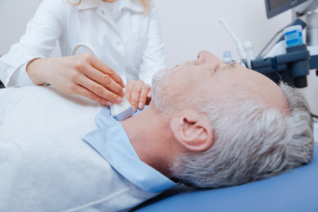Aged patient getting ultrasound of thyroid in the clinic