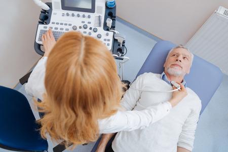 Médico competente que proporciona monitorización ultrasónica del cuerpo en el trabajo Foto de archivo