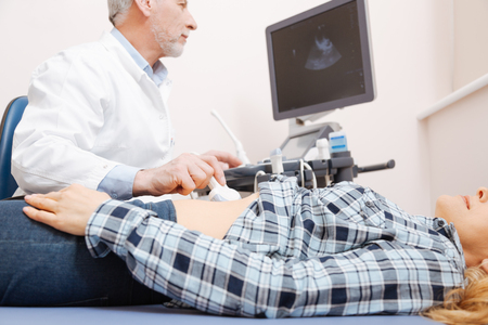 transducer: Concentrated sonographer having appointment in the medical cabinet Stock Photo