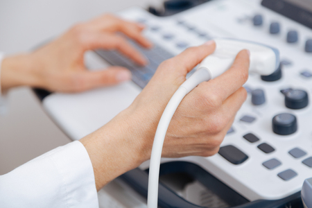 Qualified medical specialist using ultrasound equipment in the clinic