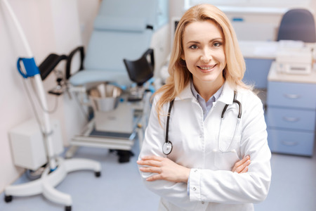 Positive mature gynecologist working in the clinic Standard-Bild