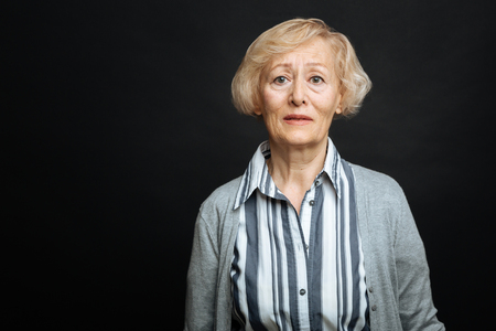 gerontology: Disappointed pensioner demonstrating sadness in the studio Stock Photo