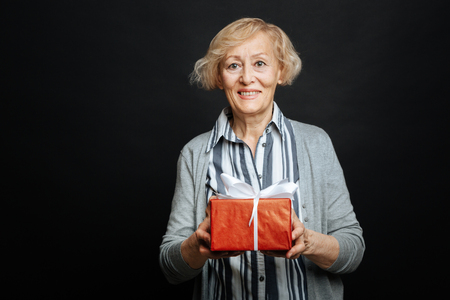 gerontology: Happy aging pensioner holding box with present in the studio