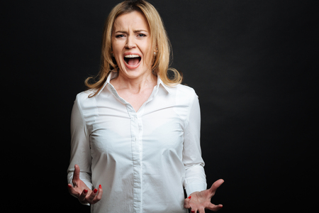 bawl: Irritated mature woman shouting in the studio