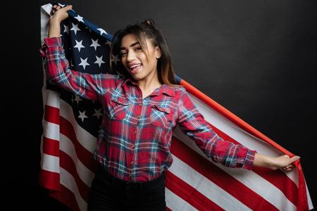 gerontology: Upbeat Hispanic American woman holding American symbol indoors