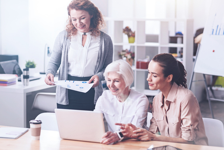 the elderly tutor: Delighted pretty women looking at the laptop Stock Photo