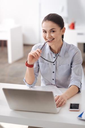 Joyful brunette holding glasses in right hand