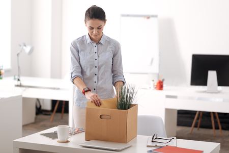 Upset female putting folder into box