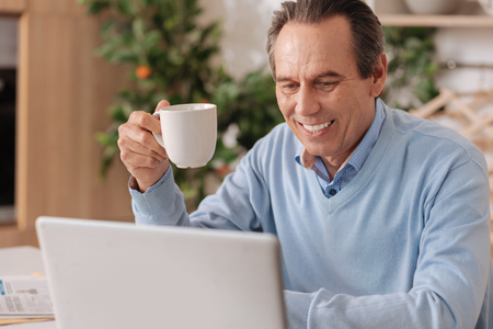 gerontology: Happy retired man using electronic gadget at home Stock Photo