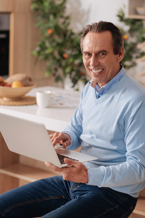gerontology: Optimistic pensioner working and using laptop at home Stock Photo