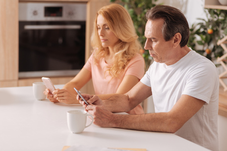 Obsessed mature couple showing addiction to the gadgets at home