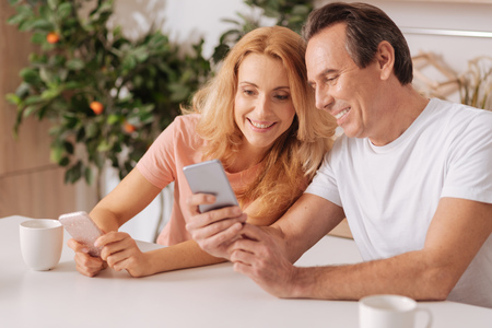 Cheerful couple using digital gadgets at home Stock Photo
