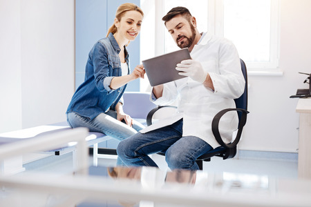 Joyful delighted woman pointing at the tablet screen Stock Photo