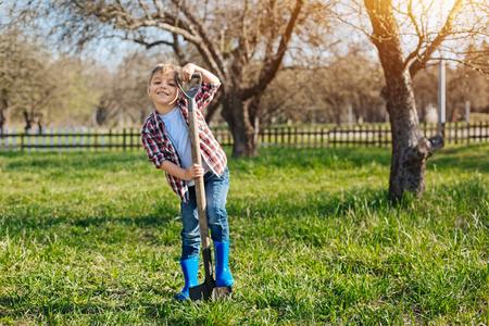 Joyful little child leaning on shovel at grandparents garden
