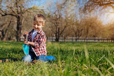 Adorable boy scooping ground in garden