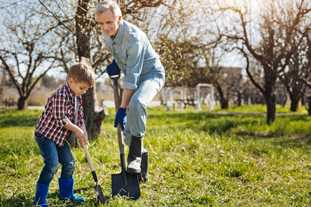 Senior gardener and his grandson digging ground together Stock Photo