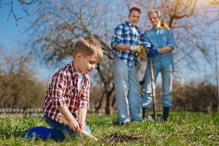 Older generation watching cute child scooping ground Stock Photo