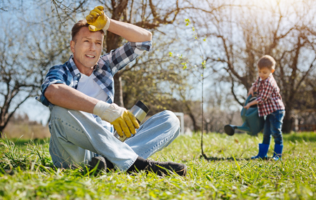 Father and son working in yard together Stock Photo