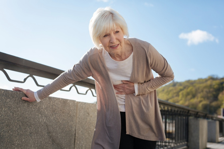 Retired woman feeling pain during the promenade