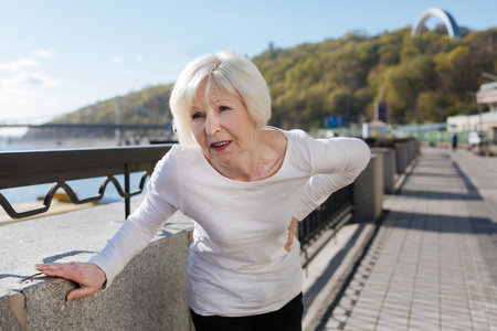 Suffering from back pain pensioner standing on the quay