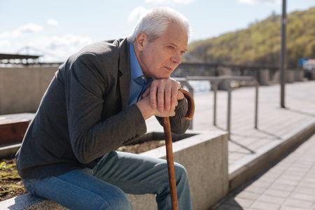 Lonely pensioner observing all around outdoors Stock Photo