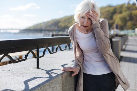 Distressing pensioner having headache in the street